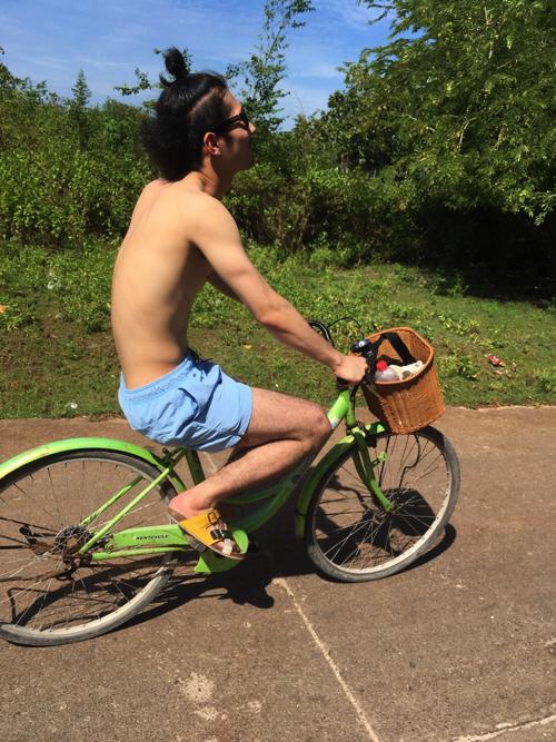 上裸で自転車に乗る男
